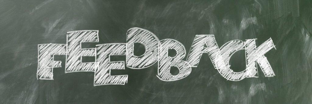la imagen muestra la palabra feedback escrita en la pizarra