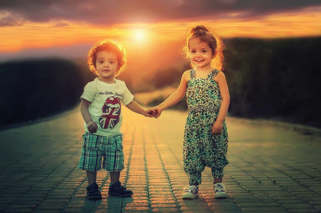 niño y niña pequeña se dan la mano en la puesta de sol