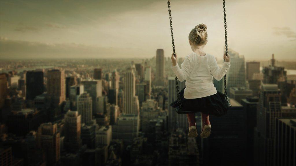 niña en un columpio en el cielo de una ciudad