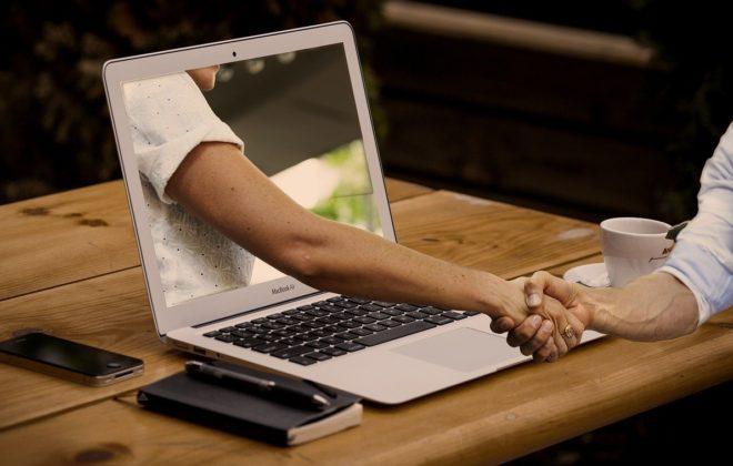 una mano sale de la pantalla del portátil y le da la mano al que escribe