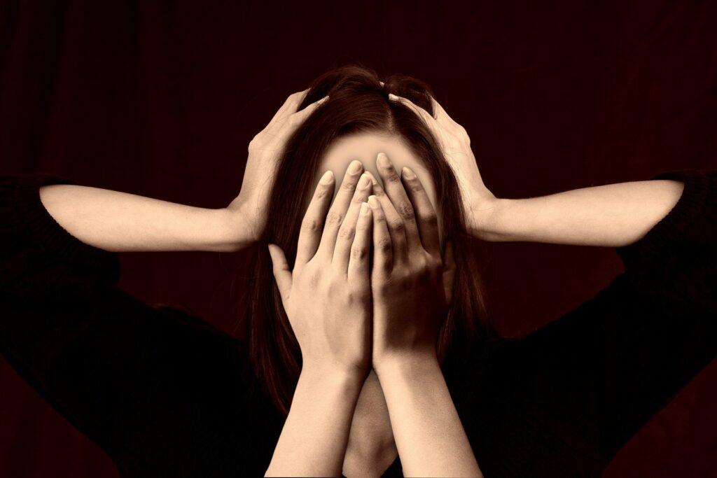 mujer tapándose la cara y dos manos le sujetan la cabeza